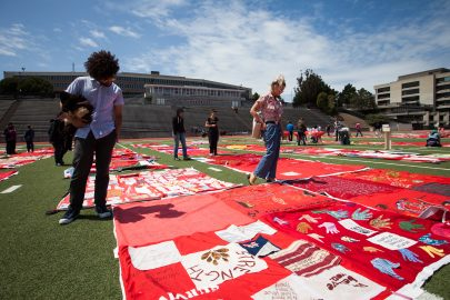 People view the exhibit of The Monument Quilt, an ongoing collection of stories from survivors of rape and abuse; the quilts are displayed on the football field of George M. Rush Stadium at City College of San Francisco Ocean Campus on Saturday, May 6, 2017.  (Photo by Ekevara Kitpowsong)