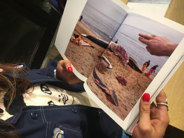 "CCSF photography student Rebecca Diablo stares at a whale carcass photo in Preston Gannaway's visual essay book, ""Between the Devil and the Deep Blue Sea"" on September 6, 2017. (Photo by Laurie Maemura)"