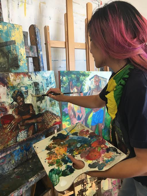 Tsungwei Moo holds her palette as she works on a painting of her late boyfriend Ricardo Distin on October 2, 2017. Photo by Laurie Maemura.
