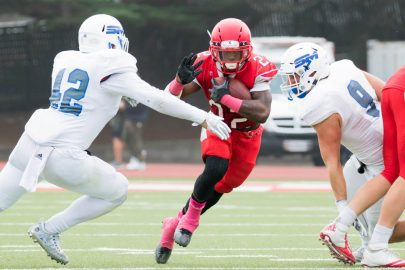 Running back Isaiah Floyd (#22) lowers his head as attempts to plow over the San Mateo defenders. Photo by Peter Wong.