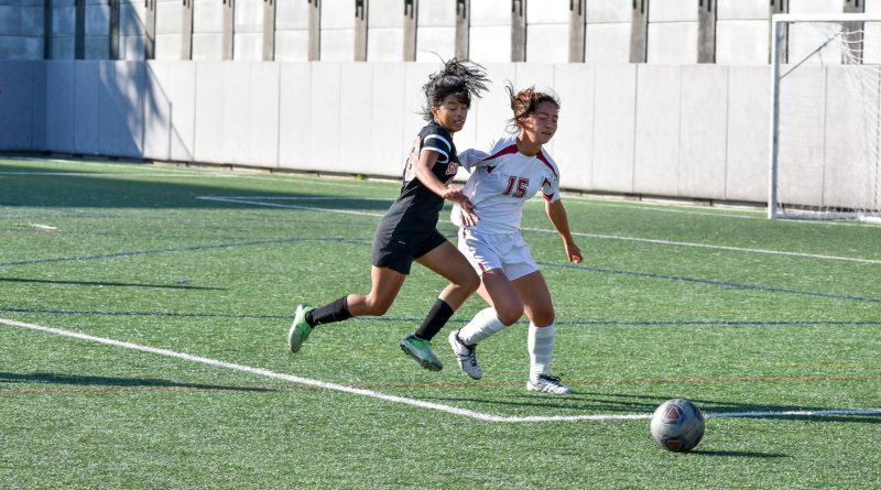 Midfielder Illena Mercado (#8)  muscles out the opponent while going after the ball. Photo by Julia Fuller.