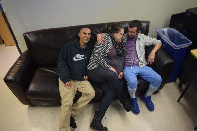HARTS student worker Juan Duran, Harts Coordinator Maraea Nauta Master and visiting CCSF student Max Cohan pose the couch within the Harts Office. Photo by Sarah Berjan.