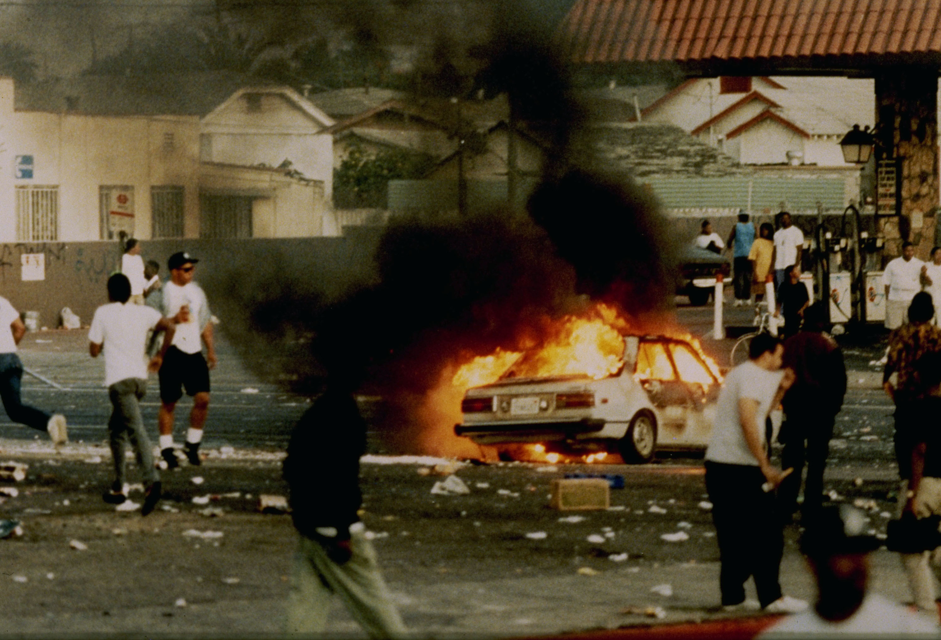 A car burns as looters take to the streets at the intersection of Florence and Normandie Avenues, April 29, 1992, This intersection is considered the flashpoint of the Los Angeles riots. (Photo by Steve Grayson/WireImage)