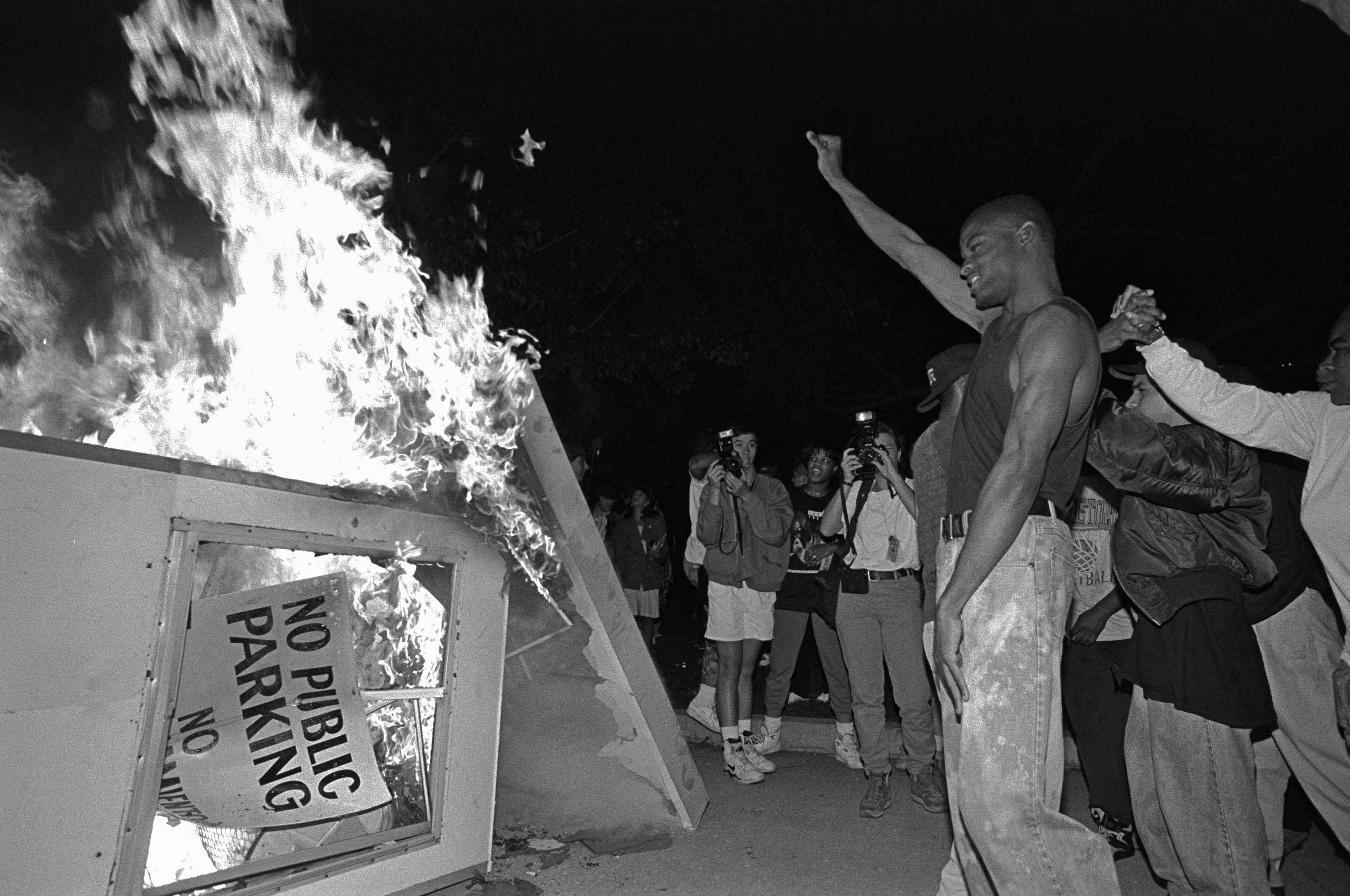 Rioters near Parker Center, LAPD headquarters in downtown Los Angeles, over turn a parking kiosk and set it ablaze. Los Angeles has undergone several days of rioting due to the acquittal of the LAPD officers who beat Rodney King. Hundreds of businesses were burned to the ground and over 55 people have been killed. (Photo by Ted Soqui/Corbis via Getty Images)