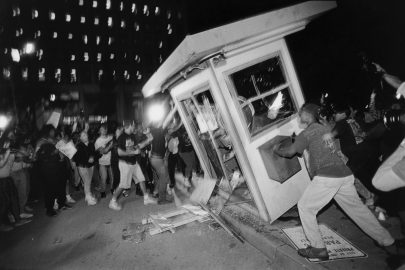 Rioters overturn a parking attendant booth at the LAPD Parker Center in downtown Los Angeles during the 1992 riots that swept the city for days after three of four police officers accused of the 1991 beating of Rodney King were cleared of all charges. The fourth officer was charged with use of excessive force. (Photo by Ted Soqui/Corbis via Getty Images)