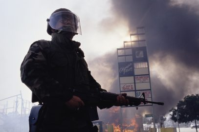 A member of the National Guard stands near burning building during the Los Angeles riots. In April of 1992, after a jury acquitted the police officers involved in the beating of Rodney King, riots broke out throughout South Central Los Angeles, killing 55 people, injuring another 2,000, and causing more than $1 billion in damage. (Photo by David Butow/Corbis via Getty Images)
