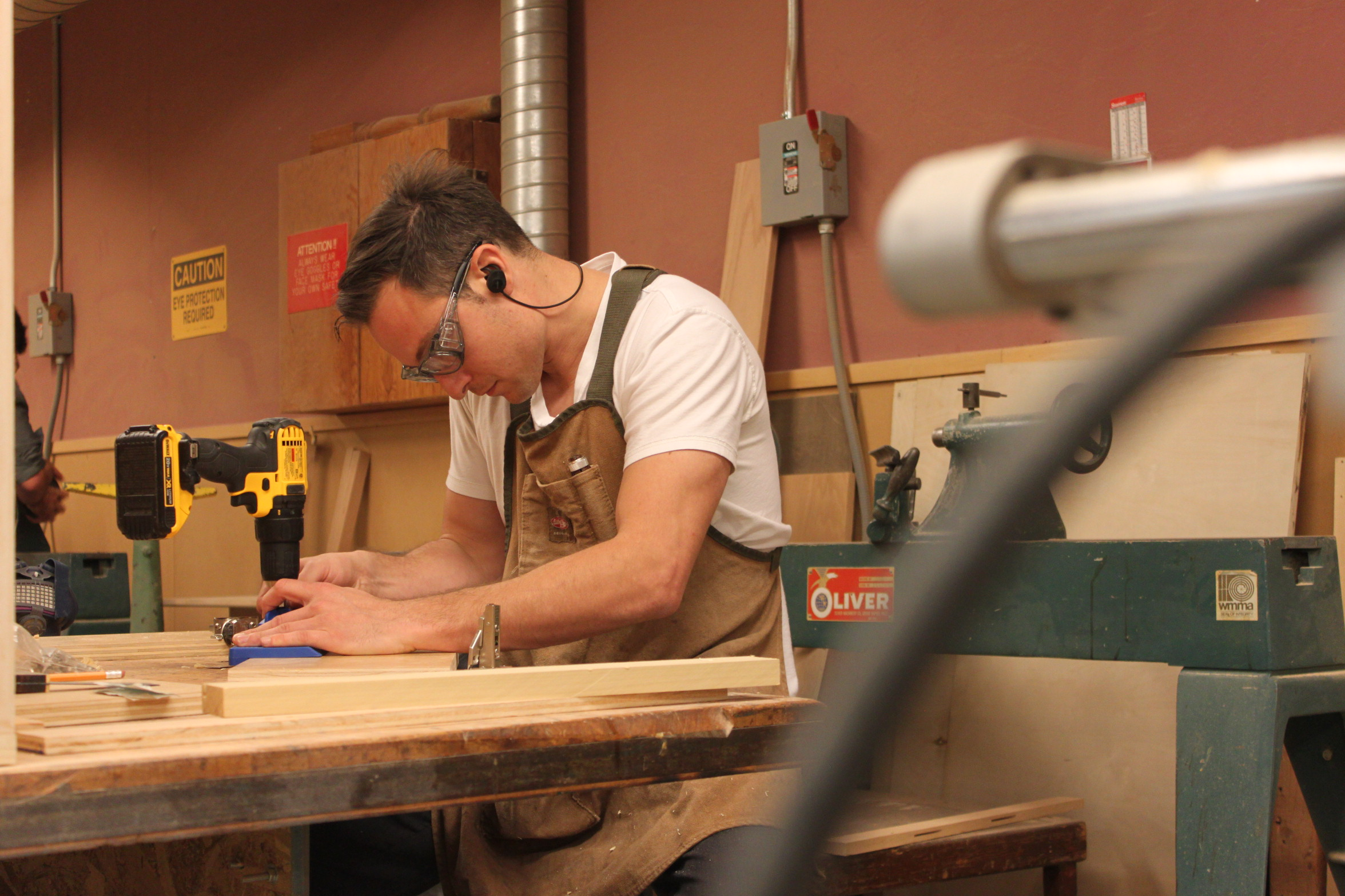 City college student Cem Turhal carefully uses a drill to place hinges on the doors he has crafted for his entertainment center. Turhal has already learned skills from the beginning carpentry class that he uses here. Photo taken by Bethaney Lee on Nov. 6, 2017.