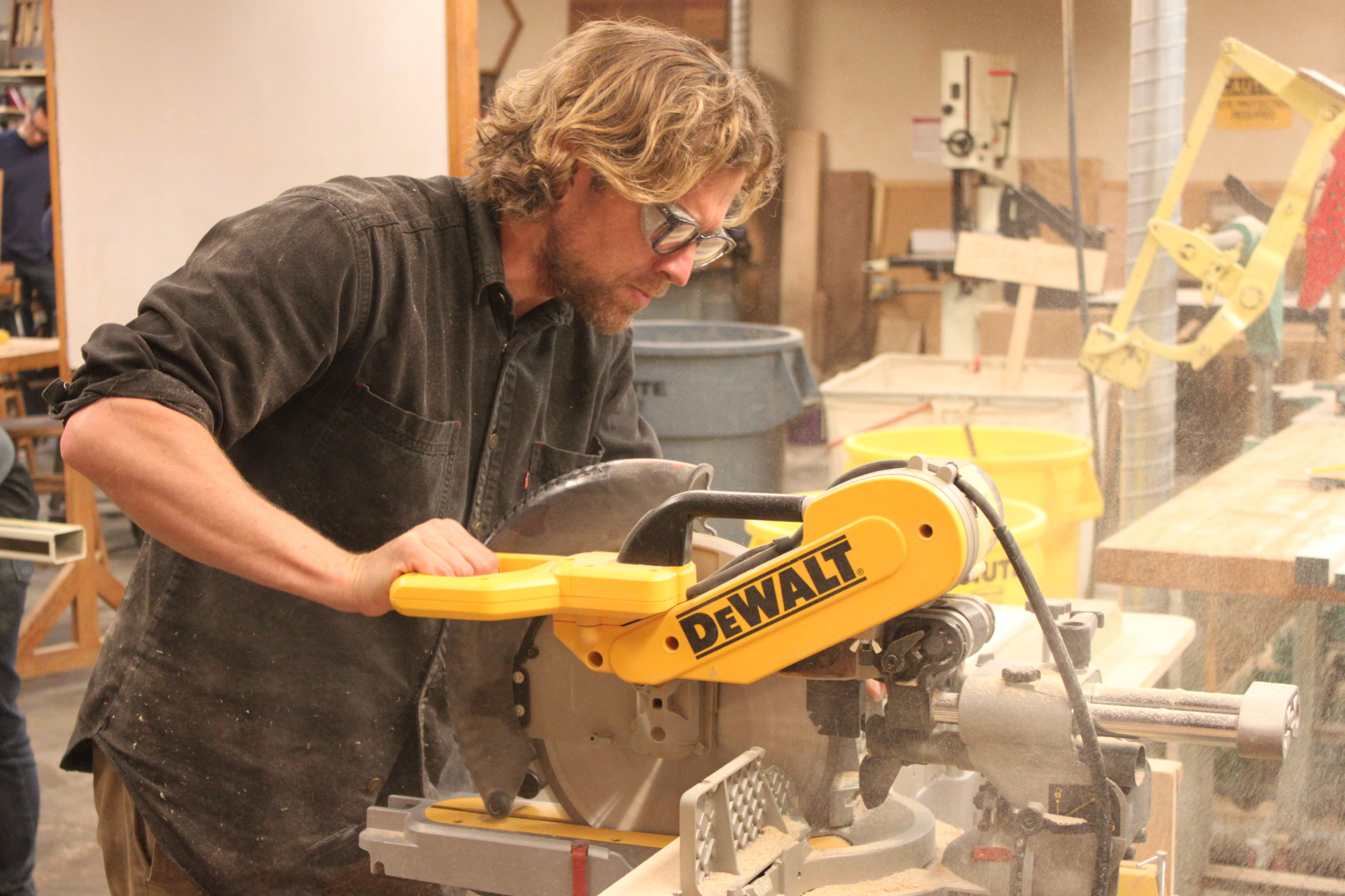 Sawdust flies as industrial design major, Trevor Rogers, works on cabinets for his apartment using a compound miter saw. Photo taken on Oct. 27, 2017.