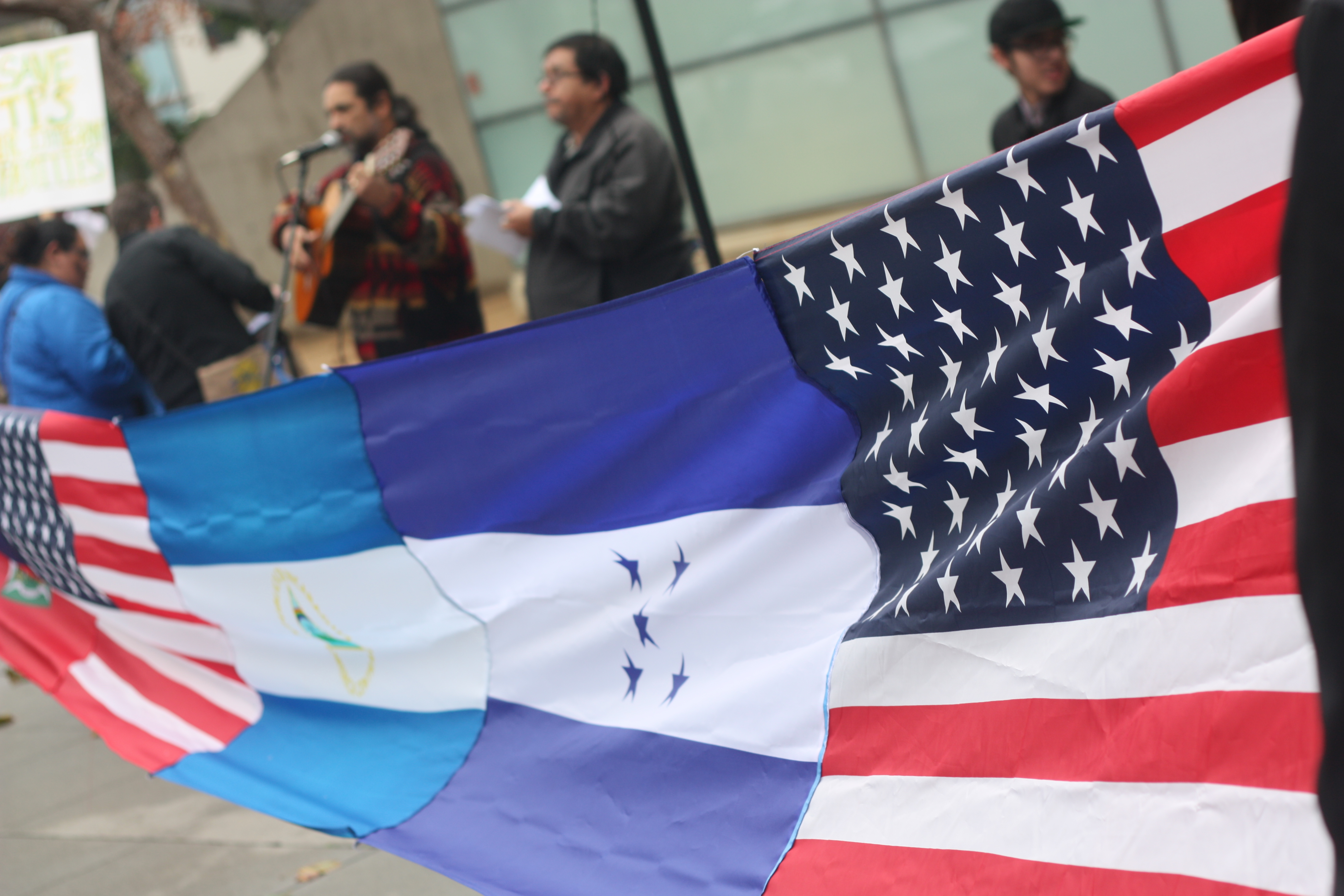 """Immigrants who participated in a """"Save TPS"""" rally held sewn flags of El Salvador, Haiti, United States and Nicaragua and Honduras in front of the San Francisco Federal Building. January 5, 2018. (Photo/Alexis Terrazas)"""