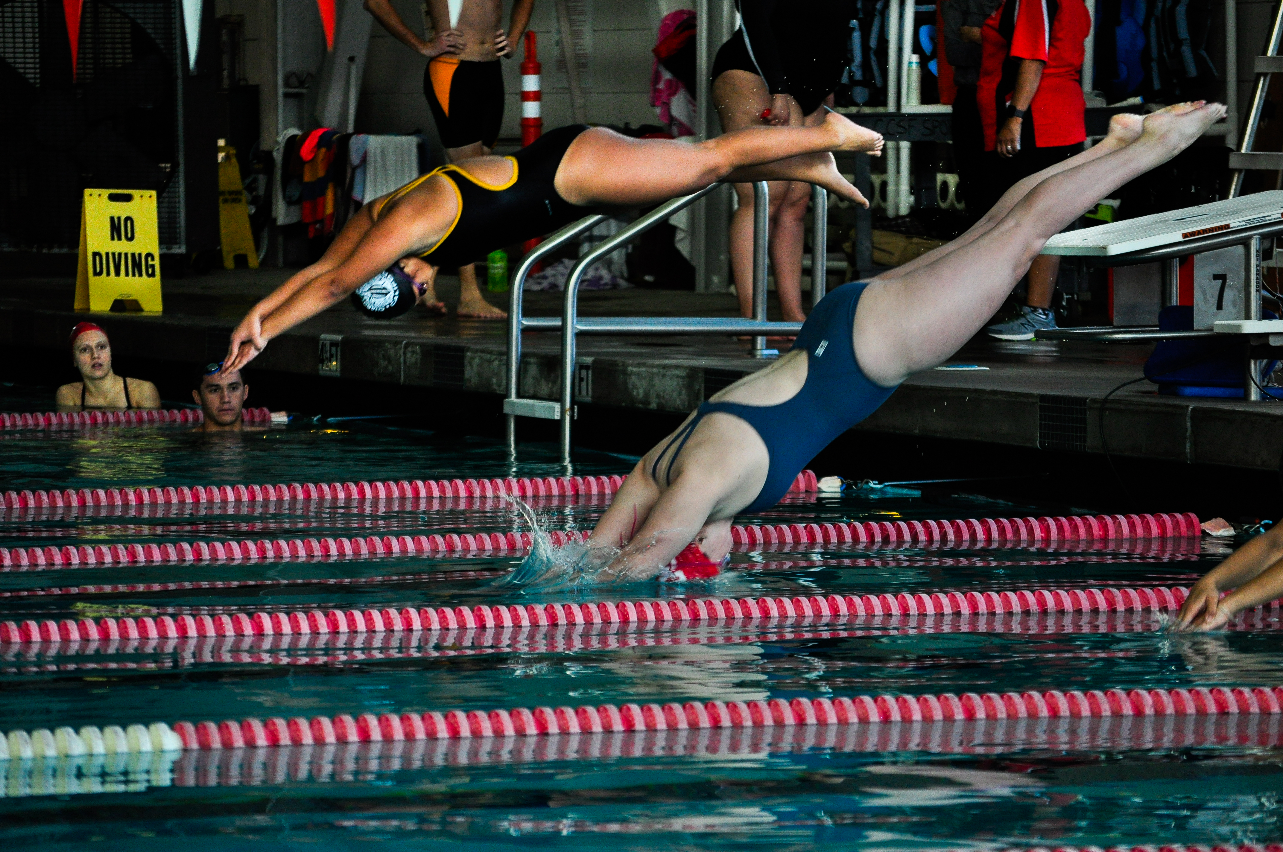 City College women's swimmer Keelin Alspaugh dives in off the block to start the Women's 100 Yard Freestyle on Feb. 2, 2018. Photo by Janeth R. Sanchez/The Guardsman.