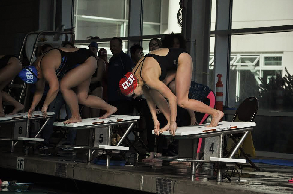 City College women's swimmer Sophia Greco (right) mounts the starting block along side Hana Wong (left) from College of San Mateo seconds before the Women's 500 Yard Freestyle on Feb. 2, 2018. She placed 1st in the heat with a new best time at 5:41.14, shaving more than a second off her previous time. Photo by Peter J. Suter/The Guardsman.