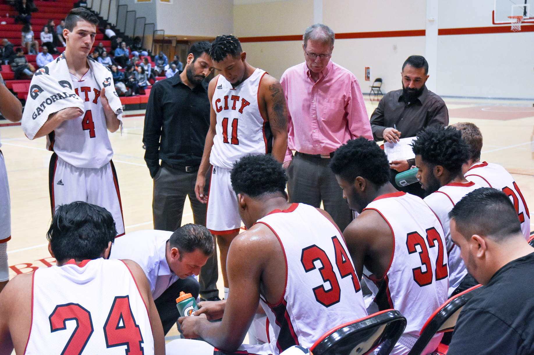 Ram's Head Coach Justin Labagh gathers men's basetball team around to run a design play against Ohlone College on Feb. 16, 2018. Photo by Michael Menaster/special to The Guardsman.