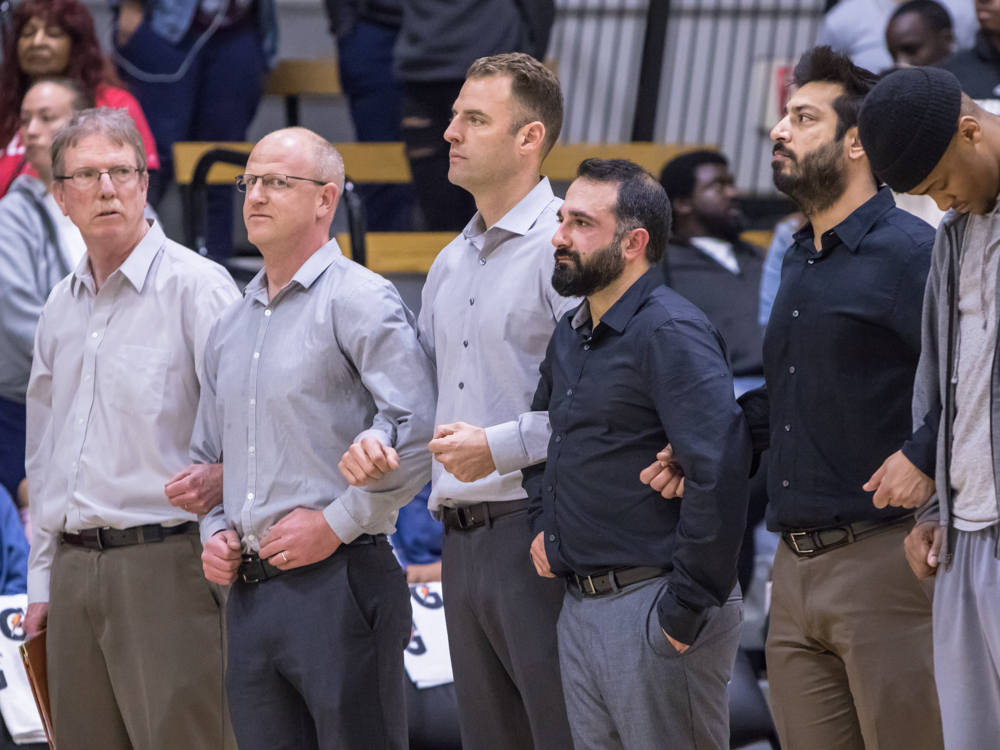 Assistant Coaches Tom McNichol (left to right), Adam D'Acquisto, Head Coach Justin Labagh (center), Nima Shaahinfar, and Ravi Bhambhra lock arms during CCCAA State Title game. Photo by Peter Wong/Special to The Guardsman.
