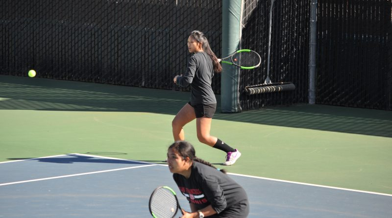 Sophomore Yvonee Ng (right) serves during doubles play with Abigail Campos (left) against Cabrillo College on March 16, 2018. Photo by Peter J. Suter/The Guardsman.