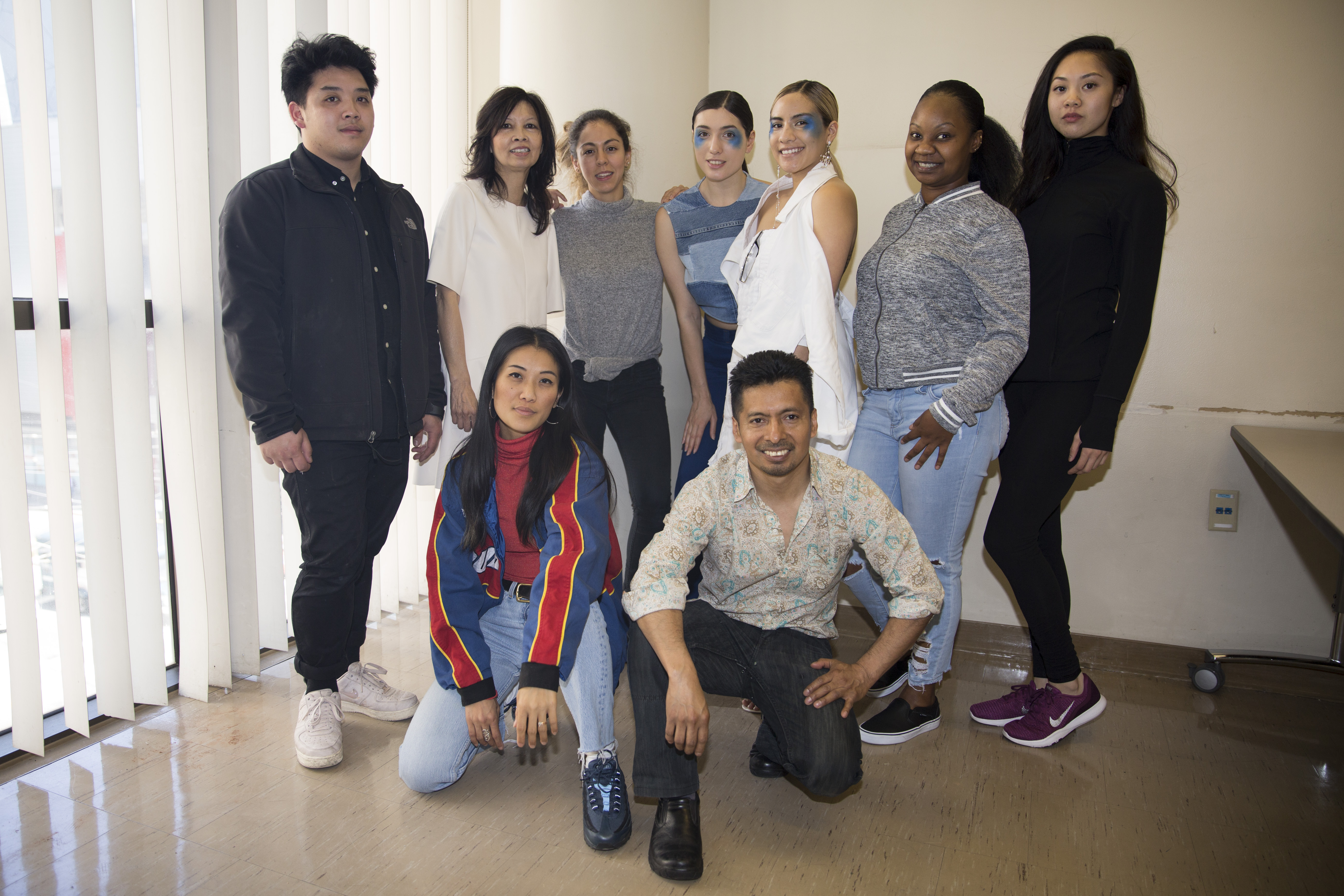 Designers, models, and others associated with the show pose in a group photo in Room 322 of Downtown Campus in San Francisco. From top left to right: Christopher Wong, Prof. Priscilla Fong, Sara Espinoza, Inna Nikolskaia, Daphne Dominia, Emerald Gilbert, Renee Gee. From bottom left to right: Natasho Lo, Enrique Chavez. Photo by Alexander Wong/Courtesy of Alexander Wong.