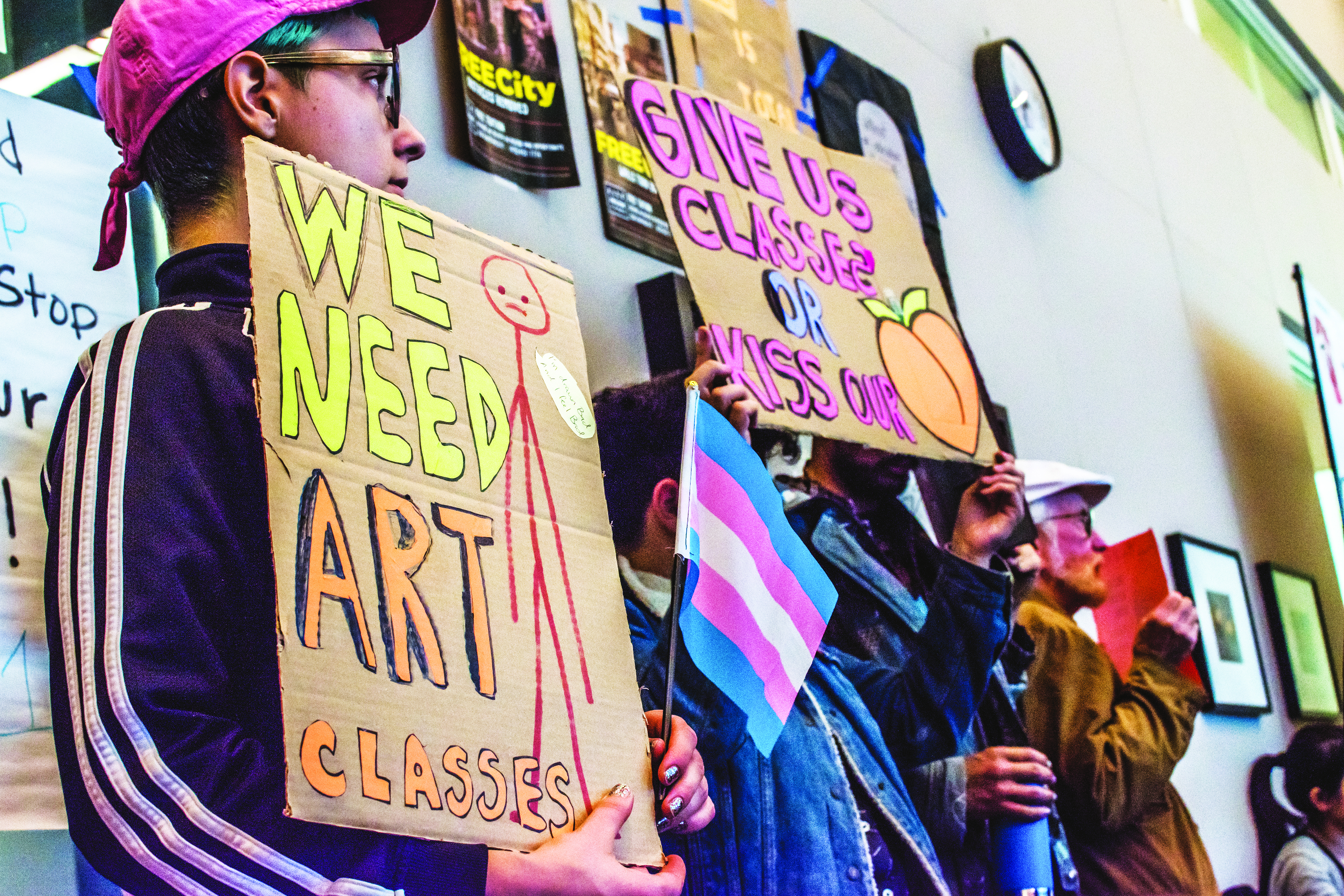 Hold Sall Vesselényi, left, protests with other students representing City College's Queer Resource Center during public comment.