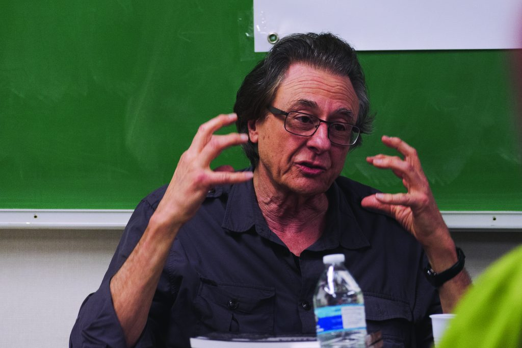 "Lou Dematteis, a San Francisco based photojournalist and filmmaker, speaks about reporting and photographing in Nicaragua during the 1985-1990 U.S.backed Contra War during City College's Journalism Matters month on October 19, 2018. The stack of books in front of him are titled""Nicaragua: A decade of Revolution"". Photo by Cliff Fernandes."